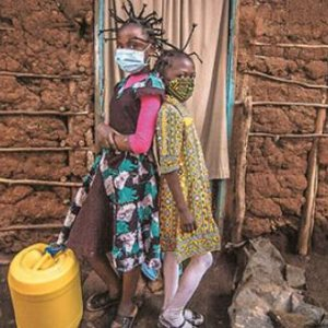 In Kibera, Nairobi, Martha Apisa and Stacy Ayuma use their braids to raise awareness of the virus by imitating its shape. Community health efforts are intense as social distancing is impossible and sanitation is poor in Kenya's largest slum.  Donwilson Odhiambo/Sopa/Zuma/Alamy