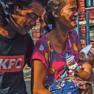The parents of one-year-old Thin  Thawdaw Tun carry their injured daughter, who  received treatment from volunteer medics. A rubber  bullet fired by the security forces hit her in the eye,  while she was inside the family home. PANOS PICTURES