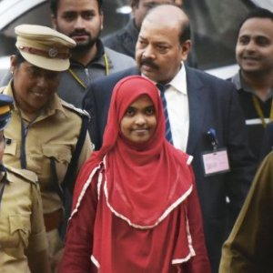 Hadiya, in the red dress, appears at the Supreme Court in New Delhi to defend her marriage to her Muslim husband Shafin in one of India's alleged 'love jihad' cases. Vipin Kumar/Hindustan Times via Getty