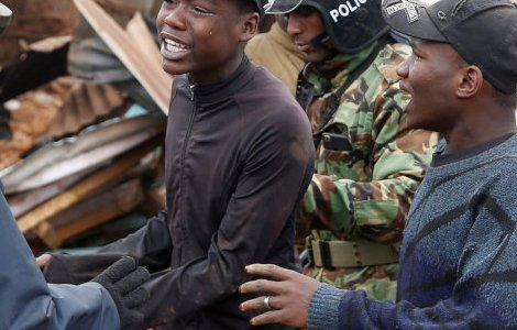A youth is escorted by Kenyan police officers as dozens of houses are being demolished to make way for a new road in the Kibera slum in Nairobi.