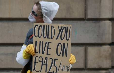 A McDonald's employee holds a banner in protest of the Statutory Sick Pay offered by the goverment as the spread of the coronavirus disease (COVID-19) continues, in London, Britain, March 23, 2020. REUTERS/Russell Cheyne