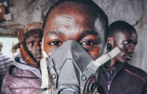 A young boy wears a gas mask to protect himself from the fumes during a fire in Kibera, the largest slum in Nairobi, Kenya. DONWILSON ODHIAMBO/Sopa Images/Lightrocket via Getty