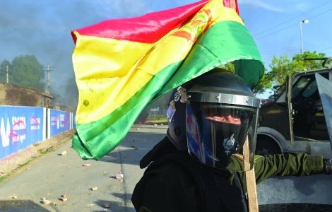 A riot police officer with a Bolivian flag is seen in Sacaba, on the outskirts of Cochabamba, Bolivia, November 15, 2019. REUTERS/Danilo Balderrama