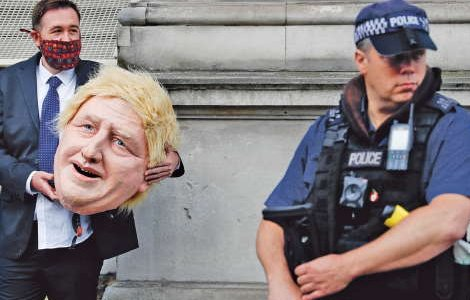 A man wears a suit and carries a large whole head mask of Boris Johnson. A police officer stands in front of him.
