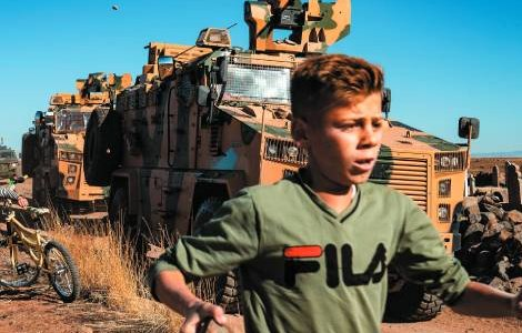 Get out! Young Kurds confront a Turkish military vehicle on patrol in northern Syria after Turkey's invasion. Delil Souleiman/AFP/Getty