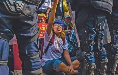 We shall not be moved! Anti-coup protesters remain seated in front of a line of riot police trying to clear roads in Yangon. Partially visible is a poster urging citizens to join the Civil Disobedience Movement. PANOS PICTURES