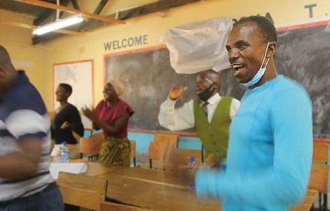 Malawi Citizens' Assembly member Daudi Amidu, a merchant trader, dances alongside fellow participants as they take a pause from considering ways to improve local spending rules in Salima South, Lake Malawi. MADALITSO BANDA/ALL HANDS ON