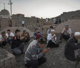 Uyghur men in Xinjiang pray during the Corban festival (Eid) in 2016. Public displays of religiosity are now considered signs of extremism. Credit: Kevin Frayers/Getty