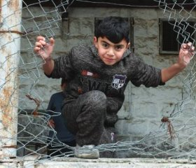 A youngster entering a soccer field through a broken fence in the H2 area.