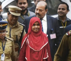 Hadiya, in the red dress, appears at the Supreme Court in New Delhi to defend her marriage to her Muslim husband Shafin in one of India's alleged 'love jihad' cases. VipinKumar/HindustanTimesvia Getty