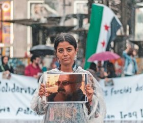 Wafa Ali Mustafa holds up a picture of her father during a demonstration on the  International Day of the Disappeared, at Alexanderplatz, Berlin. Credit: Ahmad Kalaji