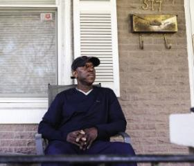 Julius sits on the porch of his house in Trenton, New Jersey, looking north at Ewing Township where foreclosure rates are drastically lower.