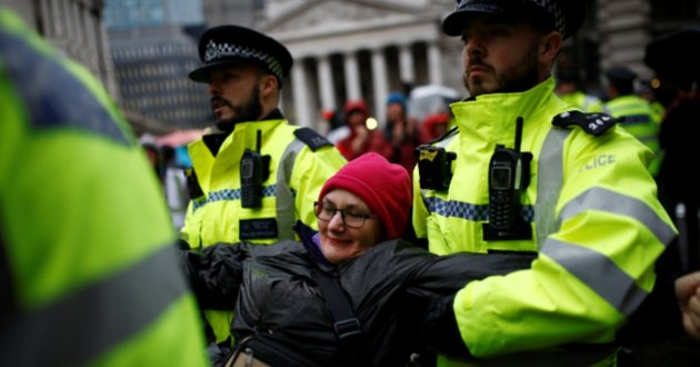 Police officers detain an activist as they block the road during an Extinction Rebellion demonstration at Bank, in the City of London, Britain October 14, 2019. REUTERS/Henry Nicholls