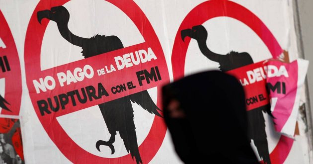 "A pedestrian wearing a face mask, as a preventive measure against the coronavirus disease (COVID-19), walks past posters on the street that read ""No to the payment of the debt. Break with the IMF"", in Buenos Aires, Argentina May 27, 2020. REUTERS/Agustin Marcarian"