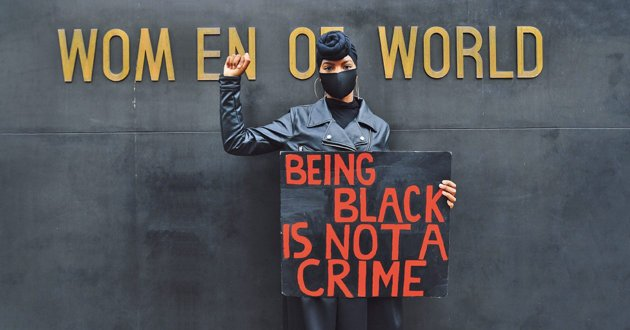 At a Black Lives Matter protest in London, following the killing of George Floyd by police in Minneapolis, US, in June 2020. The demonstrator is standing in front of a monument to the women of World War Two. DYLAN MARTINEZ/ REUTERS