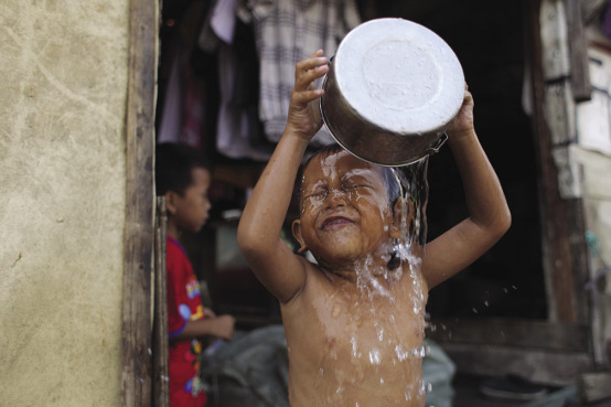 Four-year-old Rizky bathes with a can-full of water.