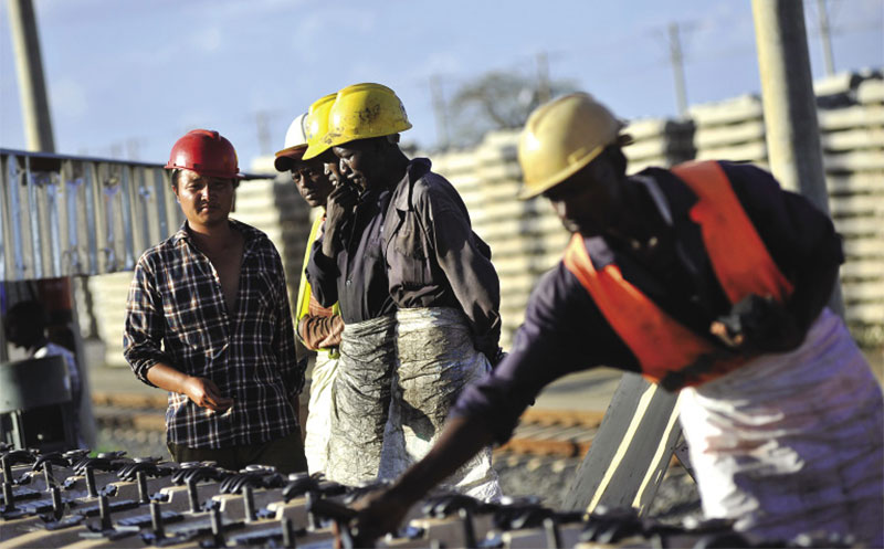 African and Chinese workers build sections for the Mombasa-Nairobi railway line, Tasaro, Kenya.