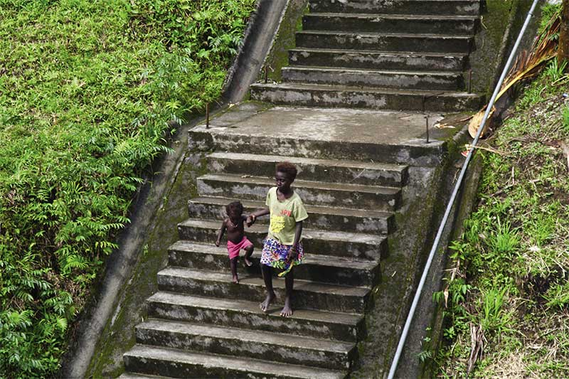 Two children descend moss-covered steps in Panguna City.