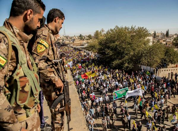 In Afrin, Kurds protest Turkeys invasion as YPG fighters look on, 24 January 2018.
