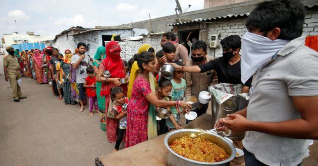 Slum dwellers receive free food during a 21-day nationwide lockdown to limit the spreading of the coronavirus disease (COVID-19), in Ahmedabad, India, March 27, 2020. REUTERS/Amit Dave