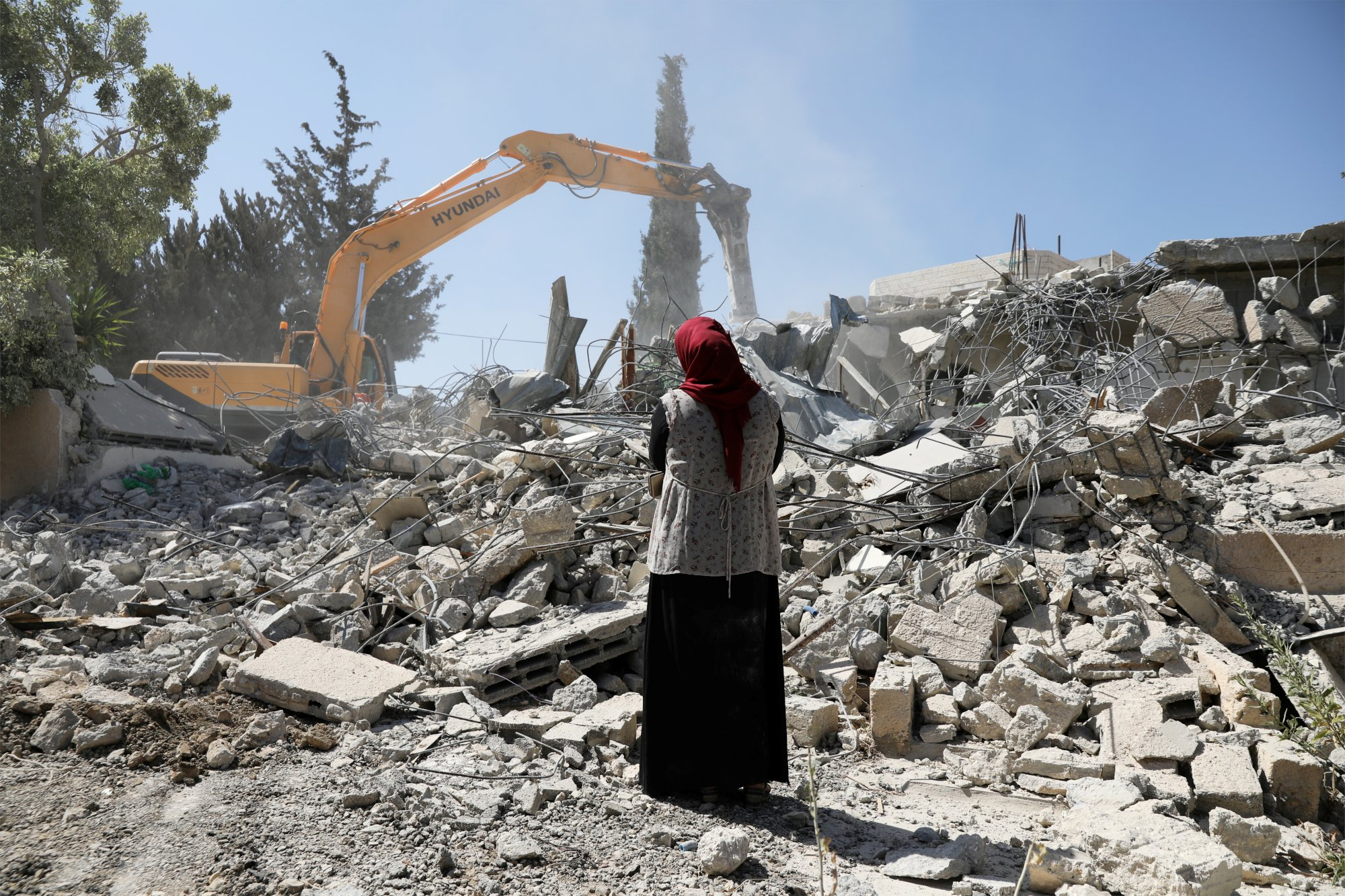 Fawzia stands on the ruins of her house, after her Palestinian ex-husband demolished the dwelling to not face the prospect of Israeli settlers moving in after he lost a land ownership case in Israeli courts, in the East Jerusalem neighbourhood of Beit Hanina, July 19, 2018. REUTERS/Ammar Awad