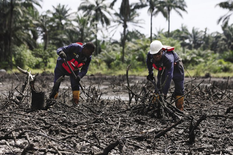 NIGERIA  Equipped with high-pressure hoses and shovels, workers remove dead mangroves and crude oil – the aftermath of two catastrophic oil spills that took place as long ago as 2008 on Bodo Creek, Rivers State, Nigeria. Backed by local communities and scientists, the comprehensive clean-up is expected to last three years. It follows a decade of legal battles and international pressure to resolve divisions between locals, the government and oil companies. The Bodo clean-up area is just 10 square kilometres in size, a small fraction of the region affected. Environmentalists fear it will take 21,000 years to rehabilitate the entire Delta.  Photo: Afolabi Sotunde/Reuters