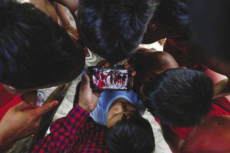 BRAZIL  Waiapi children watch a video of traditional dance on a mobile phone in Manilha, a village in indigenous territory in the Amazonian state of Amapá. The Waiapi people, who number around 1,200, are resisting moves by the Brazilian government to open up a region of pristine rainforest known as Reserva Nacional de Cobre e Associados (Renca, National Copper Reserve) to international mining companies. The Waiapi are one of the most traditional  communities in Brazil's Amazon, but modern life is edging nearer and the forest dwellers use technology to help them navigate between two worlds. Photo: Apu Gomes/AFP/Getty