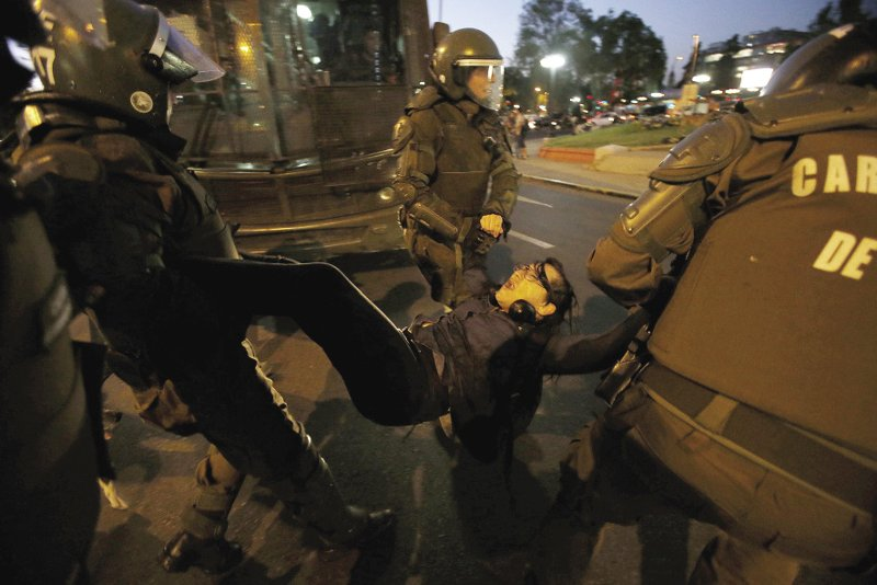 ChILE  A member of a feminist organization is arrested by riot police during a rally against sexual harassment and gender violence in Santiago on 24 October. In the run-up to the December elections, Chile has experienced mass protests over a wide range of issues. Despite the country's thriving economy, 61 femicides were recorded in 2017, and 36 women had committed suicide with violencia intrafamiliar (domestic violence) a prevalent issue. On 25 November, a crowd of 5,000 joined a two-hour march organized by the Chilean Network against Violence towards Women, calling for an end to gender-based violence around the world. Photo: Carlos Vera/Reuters