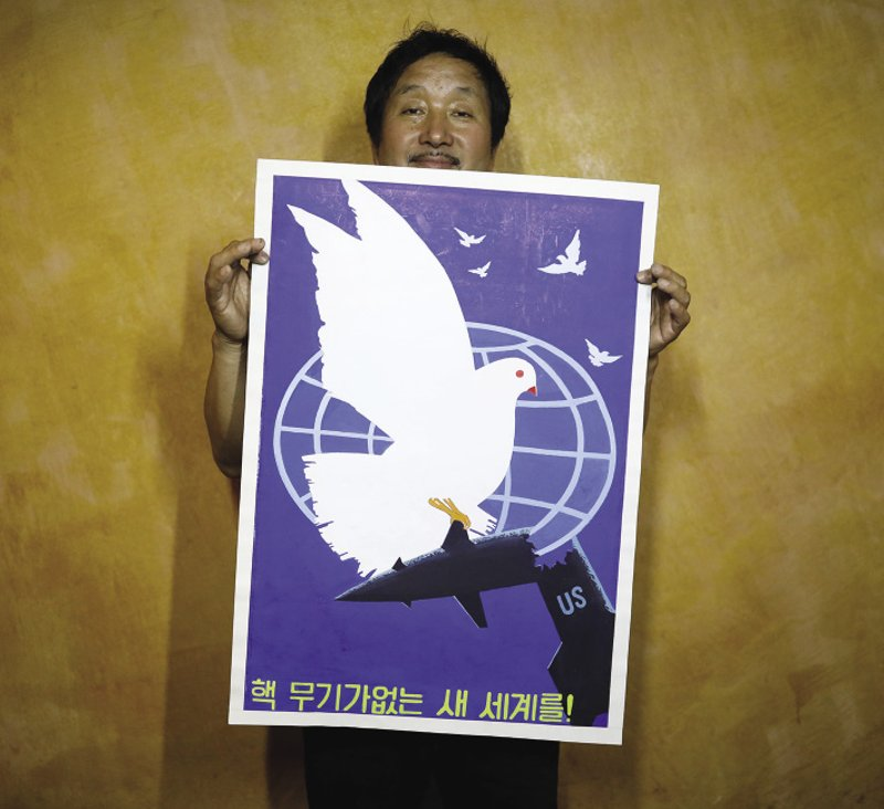 NoRTh KoREA/ChINA  Choi Sang Kyun, head of Gallery Pyongyang, poses with a North Korean propaganda poster which reads: 'For the new world without nuclear weapons!' in the Chinese border town of Dandong. The Mansudae Art Studio, run by the North Korean state, supplies work from the country's artists and sells it in China – responding to a growing demand. With all profits going directly to the state, a UN report released in February claimed that a sector of Mansudae called 'Mansudae Overseas Projects' was a front for North Korea to dodge sanctions and spend on military installations. Photo: Kim Hong-Ji/Reuters