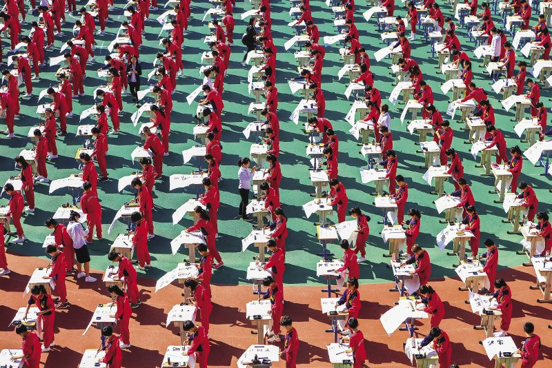 ChINA  Practice makes perfect: around 1,000 primary school students take part in a mass Chinese calligraphy class in Shenyang, Liaoning Province. In recent years, schools have been urged to offer more classes in calligraphy because computer use and textmessaging is 'ruining children's writing style'.  The digital age affords  little time for the traditional skill of hand-drawing a Chinese character with care and accuracy and dwelling  upon its meaning. Photo: VCG/Getty
