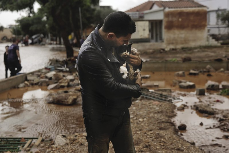 GREECE  Precious cargo: a man carries a dog and a cat he rescued from a tree following devastating flash floods in the town of Mandra, Greece, in november. Residents said the devastation was 'unprecedented' after an overnight deluge flooded industrial towns located in the foothills of a mountain just west of athens. at least 20 people lost their lives and Greece declared a day of national mourning. Rainfall on this scale is unusual in Greece and poor infrastructure leaves citizens especially vulnerable to such impacts of climate chaos. Photo: alkis Konstantinidis/Reuters