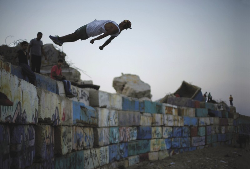 PALESTINE  An escape of sorts: a Palestinian youth demonstrates his parkour or free-running skills at the seaport of Gaza City. According to a member of the parkour team, young people come to look at the sea to take their minds off the 'difficult situation' in the occupied territory. 'They want to go out, they want to see the world.' For now that is a pipedream. youth unemployment is over 40 per cent and until some kind of resolution can be found to the Israel-Palestine conflict, Gaza youth will remain trapped and frustrated. Photo: Mohammed Salem/Reuters