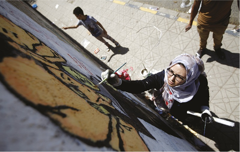 YEMEN  Street artist and activist Haifa Subay is photographed in action as she paints a mural depicting the suffering of the women and children during war. The 'Silent Victims' campaign champions artists, mostly women, to use street art to express how they have been affected by war. A famine survey released in mid-November revealed that thousands of yemenis could die daily if a Saudi-led military coalition does not lift its blockade of the country's key ports. Some 2.5 million people in yemen's crowded cities have no access to clean water, increasing the risk of cholera. Photo: Mohamed al-Sayaghi/Reuters