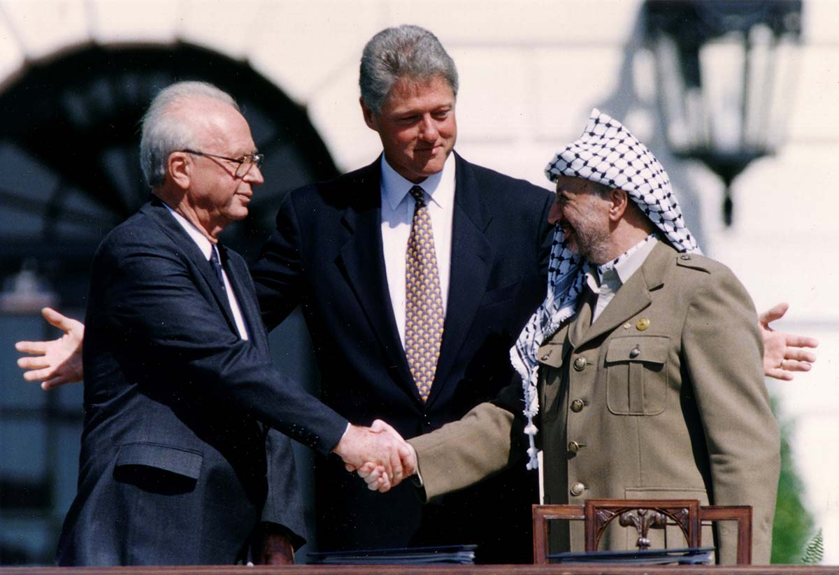 US Israel. PLO Chairman Yasser Arafat shakes hands with Israeli Prime Minister Yitzhak Rabin, as US President Bill Clinton stands between them, after the signing of the Israeli-PLO peace accord, at the White House in Washington September 13, 1993. REUTERS/Gary Hershorn/File Photo