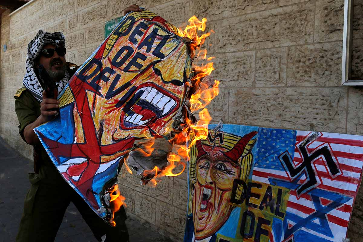 US Israel A Palestinian man burns a painting depicting U.S. President Donald Trump during a protest against Bahrain's workshop for U.S. peace plan, in Gaza City, June 24, 2019. REUTERS/Mohammed Salem