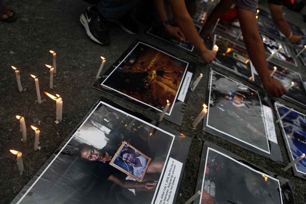 People light candles for victims of extrajudicial killings at a protest at the national police headquarters in Quezon City.