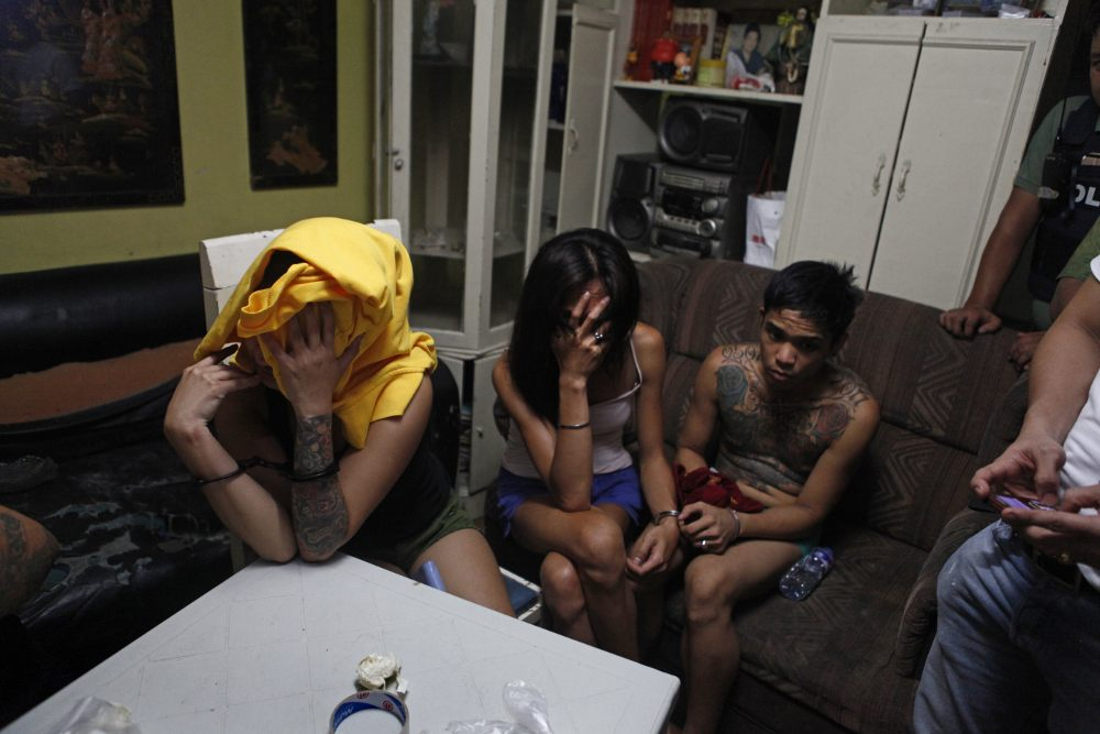 Philippine prisons: drug suspects hiding their faces when they are arrested at their home in Pasay, Manila.