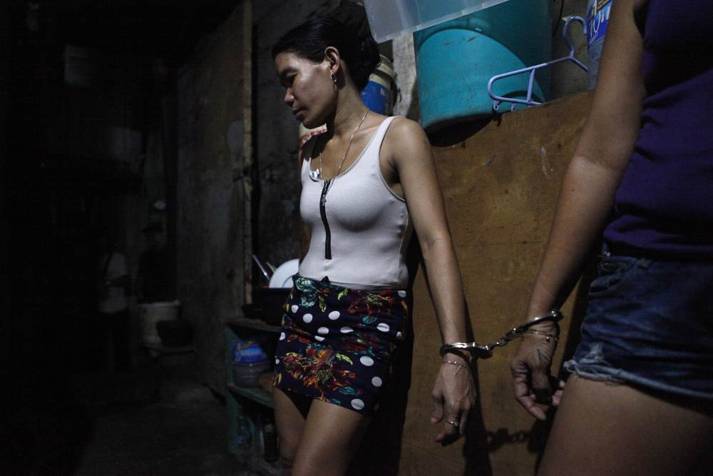 Women waiting to be transported after their arrest in their house in Quezon City, which was allegedly used as a drug den.