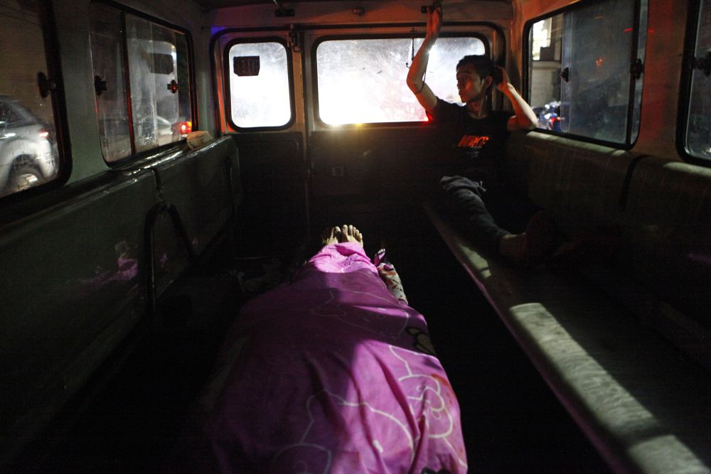 A funeral parlour transports the body of a shooting victim from the crime scene.