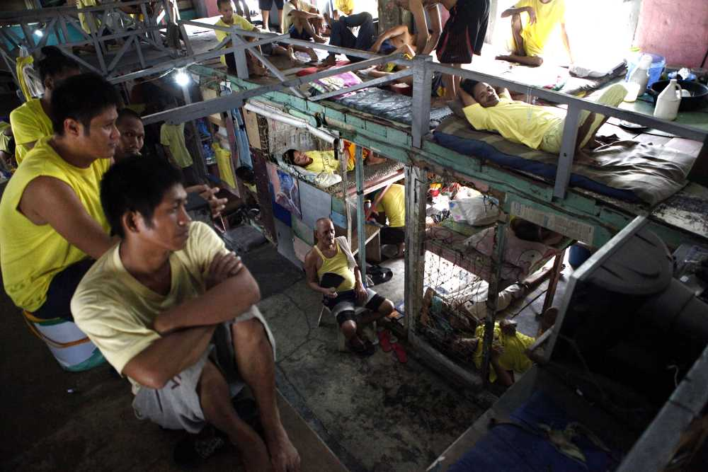 Philippine prisons: Inmates watch TV from their beds in Manila City Jail.