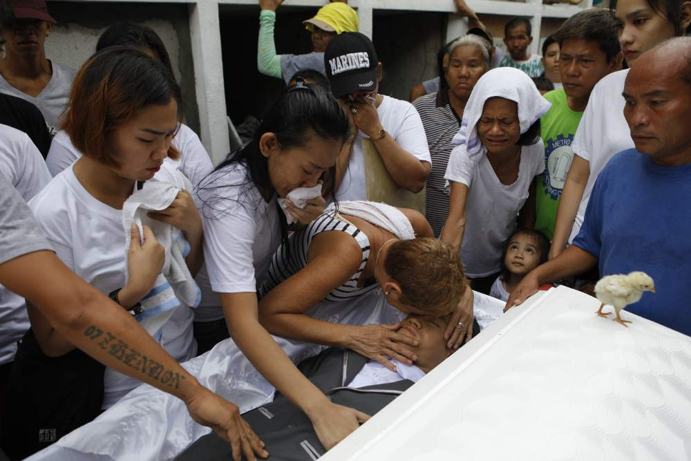 Relatives kiss Bryan Delos Reyes Dellarosa (26) in his coffin. Bryan was a drug addict and was killed in a police operation.