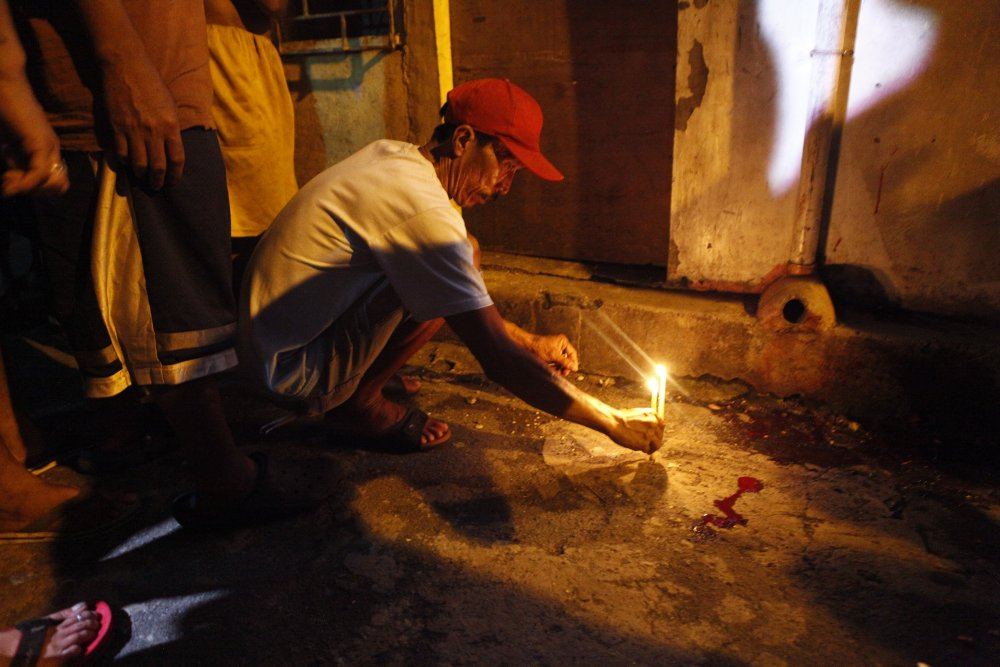 A man lights a candle in the street where fifteen bullets killed a suspected drug pusher.