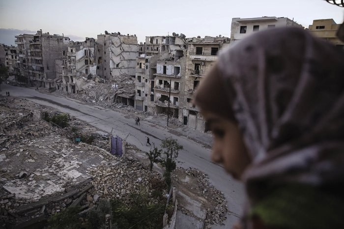 Portraits of three Syrian cities: Huossen Hamod's daughter looks out from a fifth floor balcony onto their decimated neighbourhood of  Ansari al-Sharki, Aleppo.
