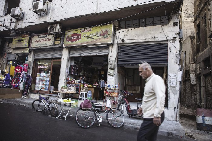 Portraits of three Syrian cities: A man walks past a newly reopened shop in Homs.