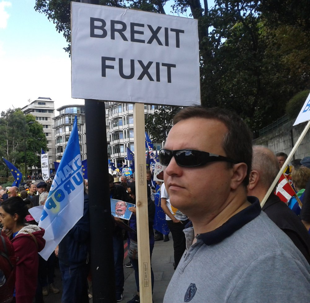 A man holds a placard bearing the words 'Brexit Fuxit'
