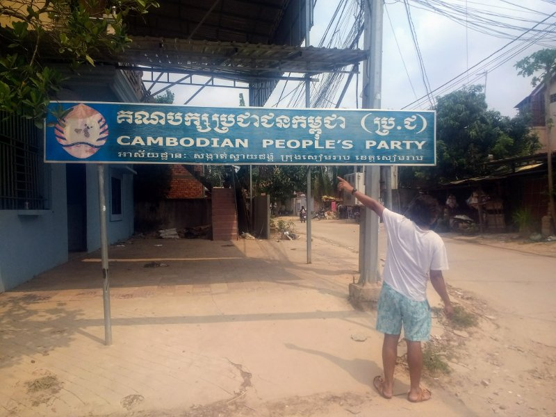 A local points out one of the many billboards advertising the ruling Cambodia People's Party.