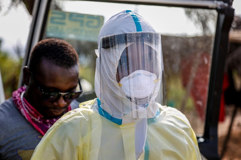 Alfred Kelfala, part of the roving Freetown Ebola burial team, puts on a safety suit before burying a corpse, 2015. Photo: Simon Davis/DFID, CC-BY-2.0