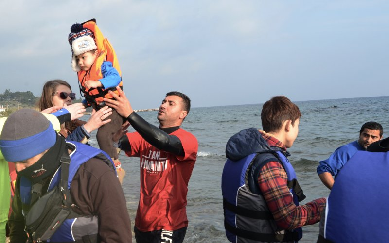Salam Aldeen handing a child who had been rescued from the dinghy to other volunteers. Volunteers take care of the children, until the parents manage one by one to leave the boat. 16 December 2015, Lesbos, Greece.