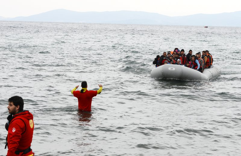 Salam Aldeen, half in the water, guides the overcrowded inflatable dinghy to safety on the beach; if the boat does not arrive nose-on to the beach, there is a danger of capsizing. Behind it is another boat, also headed for the Greek coast. 11 December 2015, Lesbos.